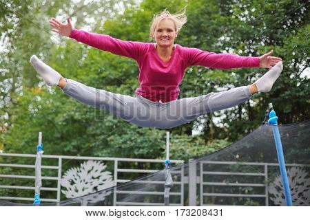 Slim smiling woman jumps on trampoline outdoor at summer day