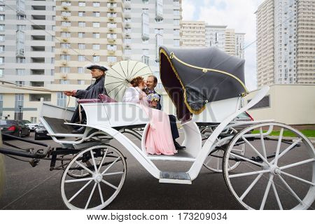 Happy pair are in coach with horse and coachman near residential buildings