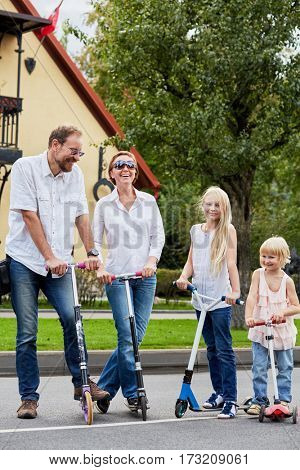 Smiling family of four stands with scooters in front of house on street.