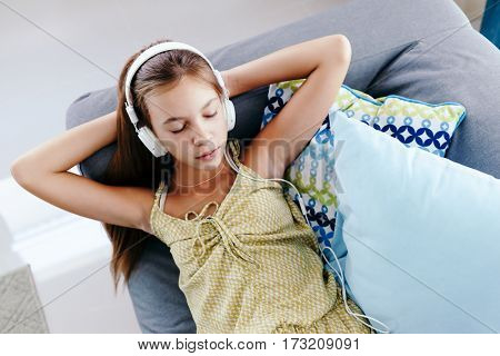 10 years old tween girl relaxing on a couch, listening to music in headphones and playing with tablet pc. Child chilling on the sofa in living room. View from above.