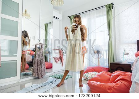 10 years old pre teen girl choosing outfit in her closet. Messy in the bedroom, clothning on the floor. Teenager is dressing up and singing in the morning.