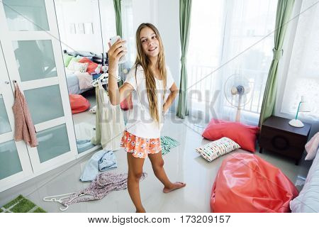 10 years old pre teen girl choosing outfit in her closet. Messy in the bedroom, clothing on the floor. Teenager is dressing up and taking selfie in the morning.
