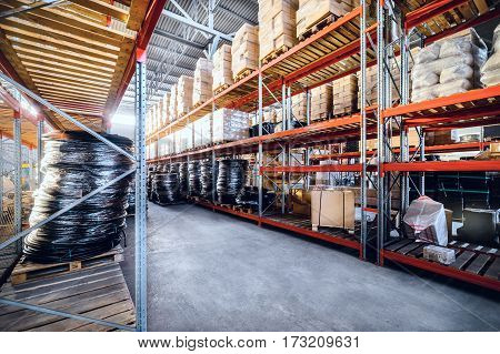 Large industrial warehouse. Long shelves with a variety of boxes and containers. Toning the image.