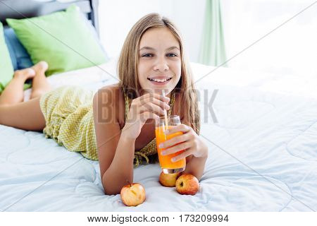 10 years old pre teen girl drinking orange juice while relaxing in bedroom. Healthy food for breakfast.