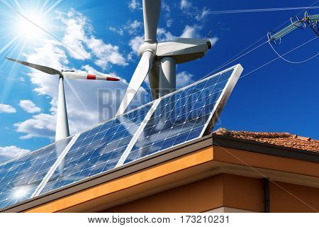 Close-up of a house roof with a solar panels on top and two wind turbines on a blue sky with clouds sun rays and a power line