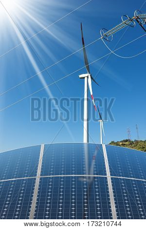 Group of solar panels with wind turbines and a power lines on a clear blue sky with sun rays. Solar and wind energy