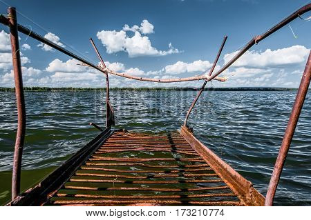 Old rusty metal footbridge on the lake. Sunny day, blue sky and white clouds.