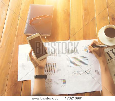 Business Male manager discussion ideas and writing business plan at workplace,man holding pens and papers for business data,notes documents,analysis chart at the table,vintage color,selective focus.