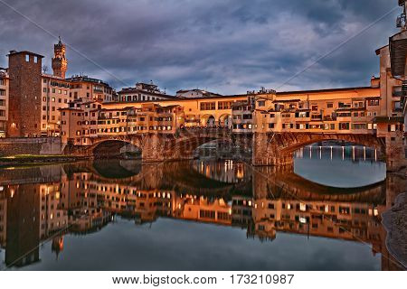 Florence, Tuscany, Italy: view at twilight of the landmark Ponte Vecchio the famous medieval bridge over the Arno river with old shops of artisan goldsmiths and jewelers