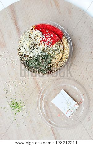 One jar with colorful mix of oriental spices. In light wooden cutting board.