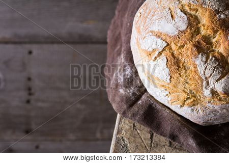 Freshly baked traditional bread on wooden table. View from above