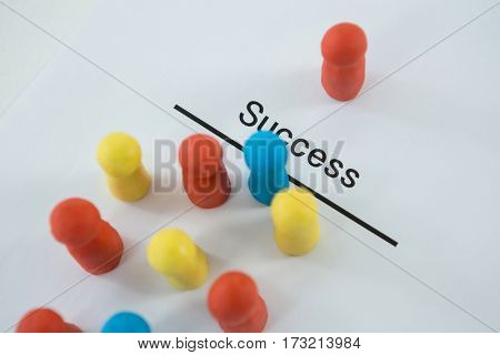 Multicolored figurines on a white paper with text success against white background