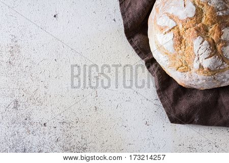 Freshly baked traditional bread liying on brown kitchen towel on white rustic background. View from above