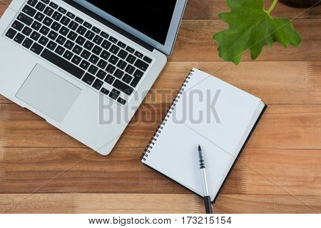 Diary, pen and laptop on a wooden table