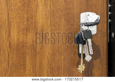 Close-up of bundle of different keys in key hole in wooden texture door.