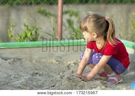Little Girl Playing In Sandbox On A Sunny Summer Day