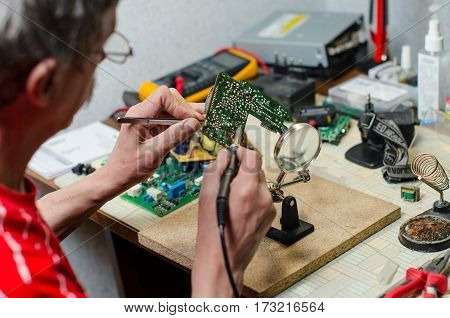 Electronic technician repairs mobile phone using soldering iron tweezers and magnefier