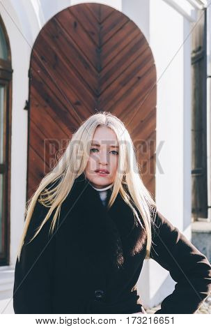 Young beautiful blonde girl staying near the wood door