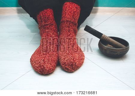 Man in a red woolen socks sitting on the floor in the yoga studio with a singing bowl