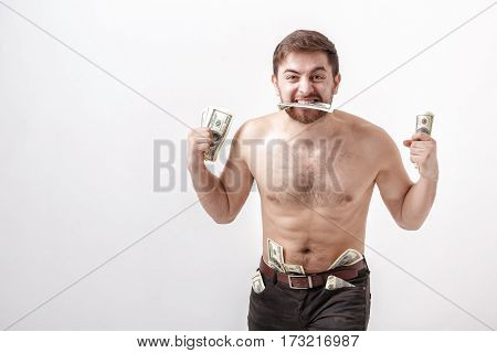 young handsome brunette man with a beard eating a hundred dollar bill. money and greed