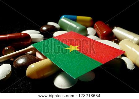 Burkina Faso Flag With Lot Of Medical Pills Isolated On Black Background