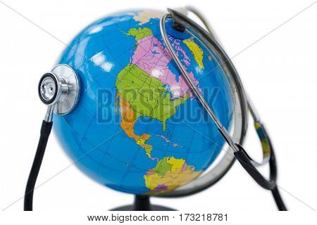 Close-up of globe being check with stethoscope on white background