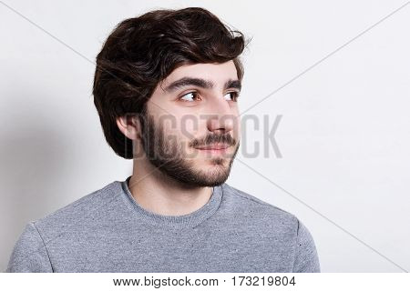 A close-up of stylish hipster with trendy beard and hairstyle dark big eyes dressed in casual clothes looking happily aside. Portrait of handsome man with beard over white background