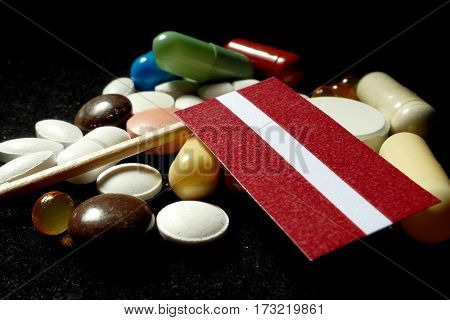 Latvian Flag With Lot Of Medical Pills Isolated On Black Background