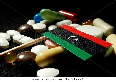 Libyan Flag With Lot Of Medical Pills Isolated On Black Background