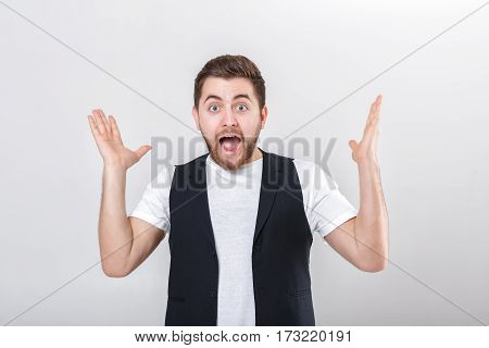 portrait of young attractive surprised brunette man in white shirt on gray background. surprising fact