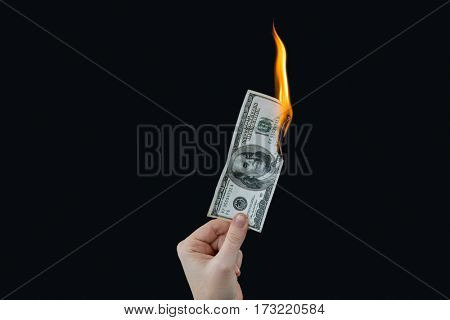 Hand holding hundred dollar bill on fire against black background