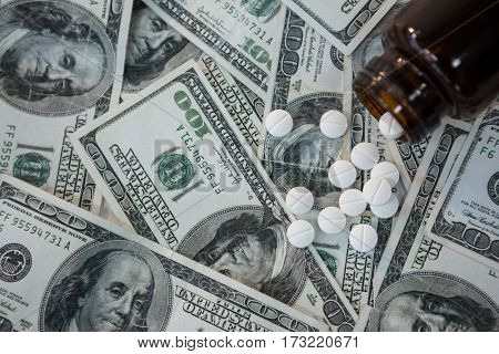 Close-up of pills spilling on currency notes
