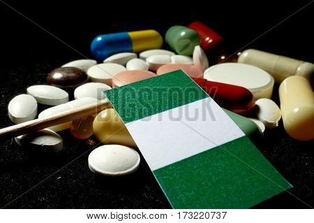 Nigerian Flag With Lot Of Medical Pills Isolated On Black Background