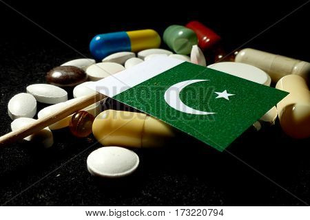 Pakistani Flag With Lot Of Medical Pills Isolated On Black Background