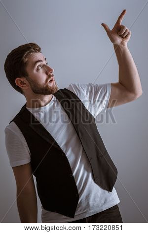 profile portrait of handsome man with beard pointing copy space. young man in t-shirt  pointing away against grey background