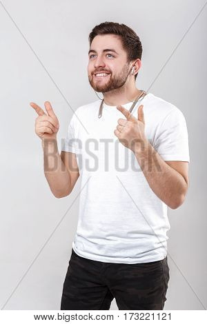 young handsome man with a beard in a white t-shirt listening to music on headphones