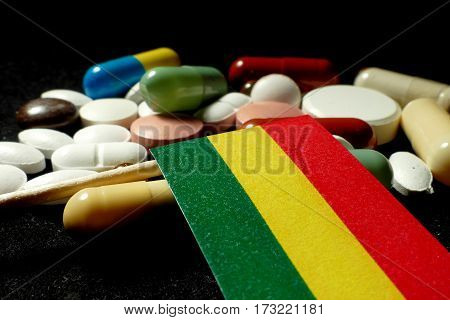 Bolivian Flag With Lot Of Medical Pills Isolated On Black Background