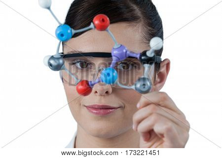 Portrait of female scientist holding molecular model against white background