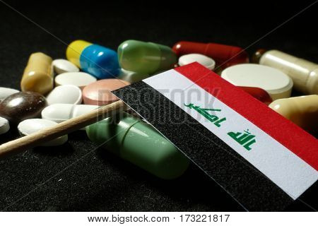 Iraqi Flag With Lot Of Medical Pills Isolated On Black Background