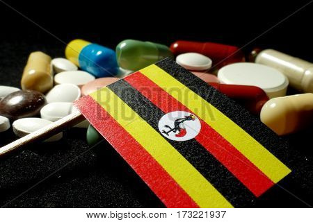 Ugandan Flag With Lot Of Medical Pills Isolated On Black Background