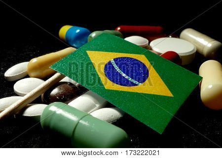 Brazilian Flag With Lot Of Medical Pills Isolated On Black Background