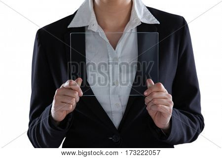 Mid section of businesswoman pretending to use digital tablet against white background