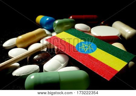 Ethiopian Flag With Lot Of Medical Pills Isolated On Black Background