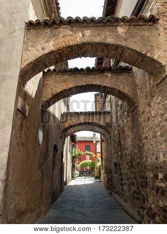 SIRMIONE ITALY - MAY 5 2016: Picturesque narrow town street in Sirmione Lake Garda Italy.