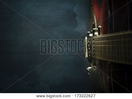 Close-up of old electric jazz guitar on a dark blue background with copy space
