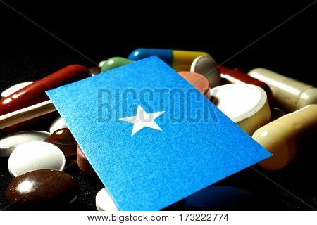 Somalian Flag With Lot Of Medical Pills Isolated On Black Background