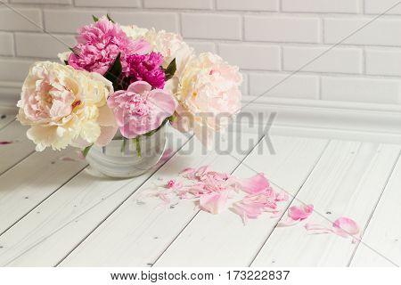 Beautiful bouquet of pink and white peonies in the glass vase with scattered petals on the light white brick and wood background.