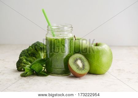 Healthy green smoothie and ingredients. Spinach smoothie in glass jar with apple, spinach and kiwi.