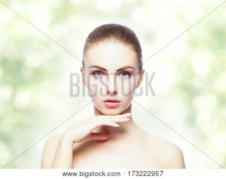 Portrait of young, beautiful and healthy woman: over greenish summer background. Healthcare, spa, makeup and face lifting concept.