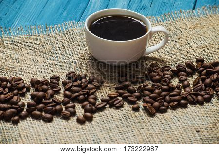 Cooked black coffee with sweet marshmallow on a blue wooden table